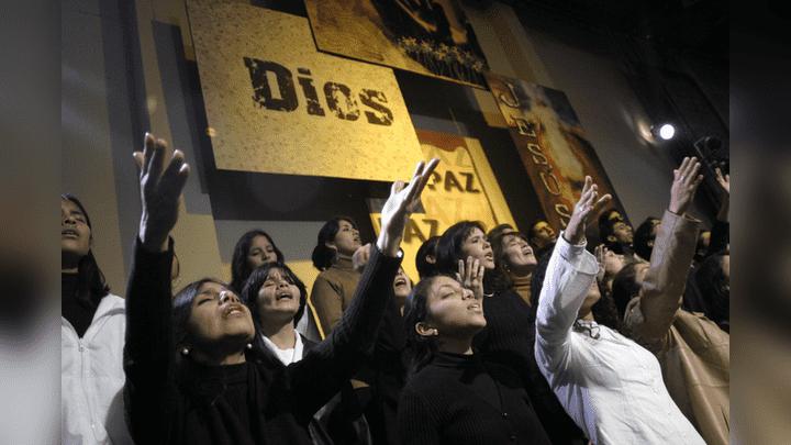 Experiencia religiosa. Cristianos oran y cantan en un culto multitudinario.
